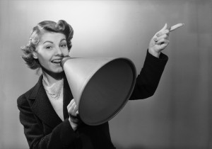 Original Caption: Portrait of a woman holding a megaphone and pointing to her left. Undated photograph.